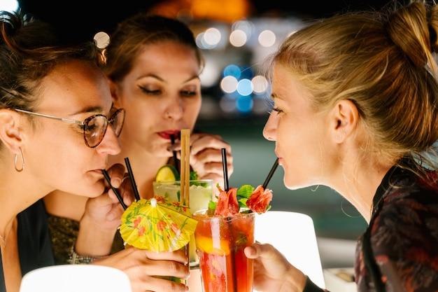Frauen, die nachts zusammen auf einer terrasse cocktails trinken