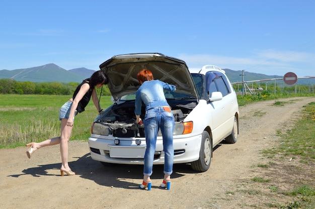 Frauen, die nahe dem kaputten auto mit geöffneter motorhaube auf einer landstraße stehen