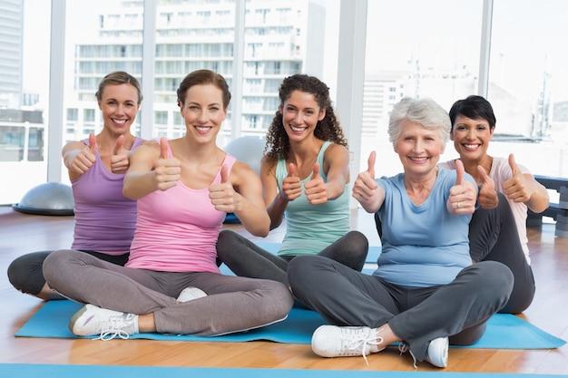 Frauen, die oben daumen in der yogaklasse gestikulieren
