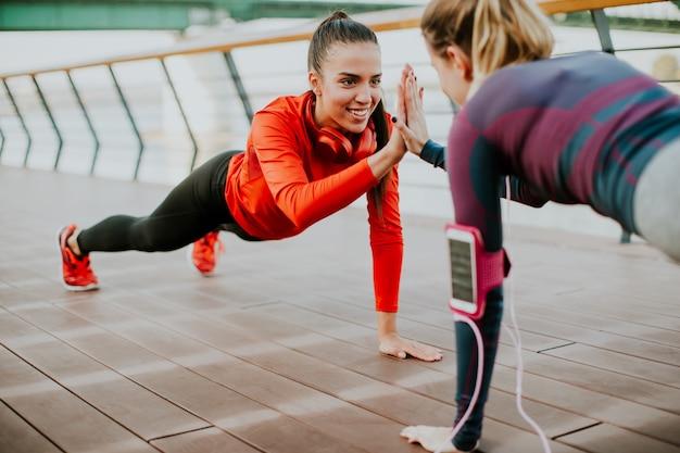 Frauen, die planke auf flussufer nachdem dem laufen tun