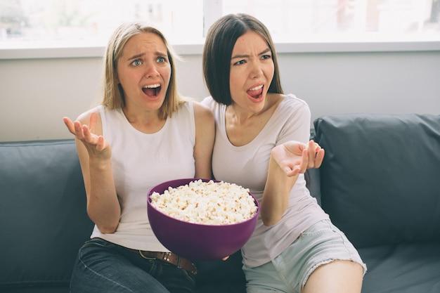 Frauen, die popcorn essen und fernsehen