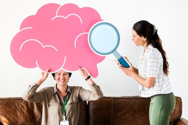 Frauen, die rosa wolkenikonen halten