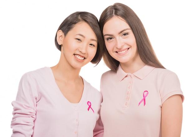 Frauen, die rosafarbene oberseiten und farbbänder für brustkrebs tragen.
