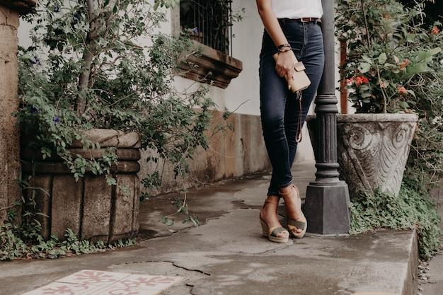 Frauen, die sandalen oder schuhe halten eine geldbörse, einen geldbeutel und eine tasche tragen