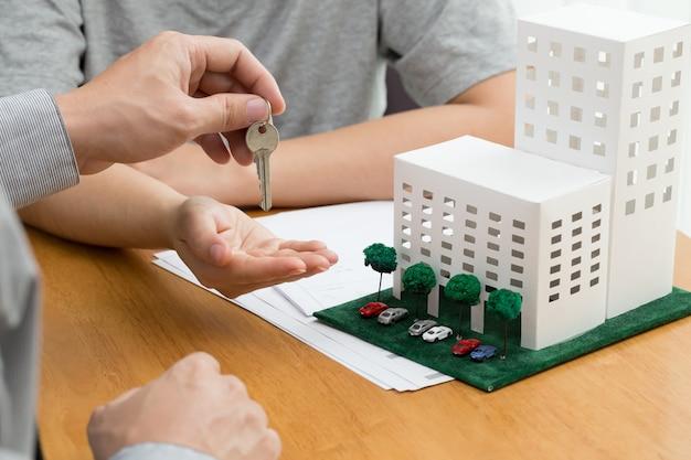 Frauen, die schlüssel vom immobilienmakler nehmen