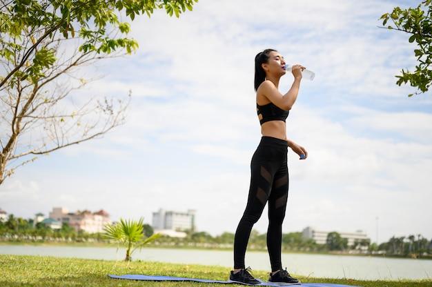 Frauen, die schwarze kleidung tragen, um wasser beim gehen und laufen zu trinken.