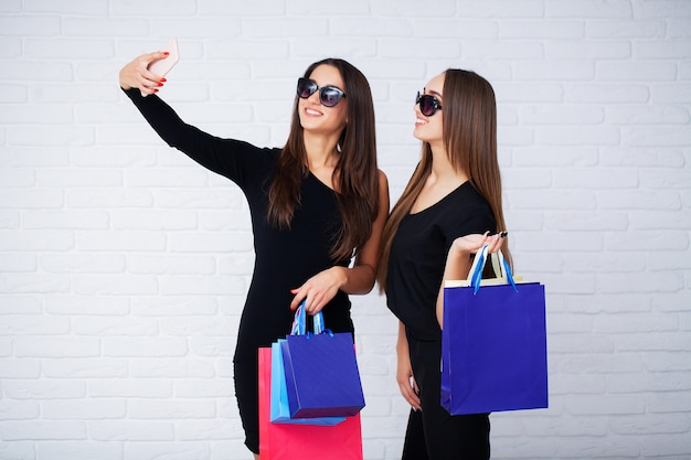 Frauen, die schwarze taschen auf licht im schwarzen freitag-feiertag halten