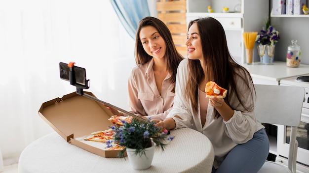 Frauen, die selfie beim essen der pizza nehmen