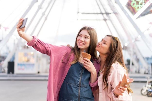 Frauen, die selfie zusammen im vergnügungspark nehmen