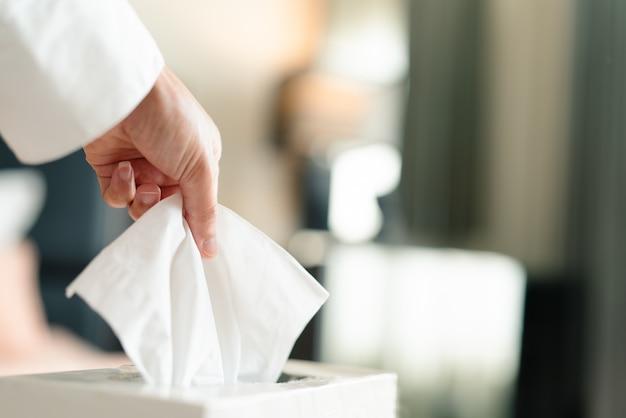 Frauen, die serviette / seidenpapier von hand von der seidenkiste pflücken