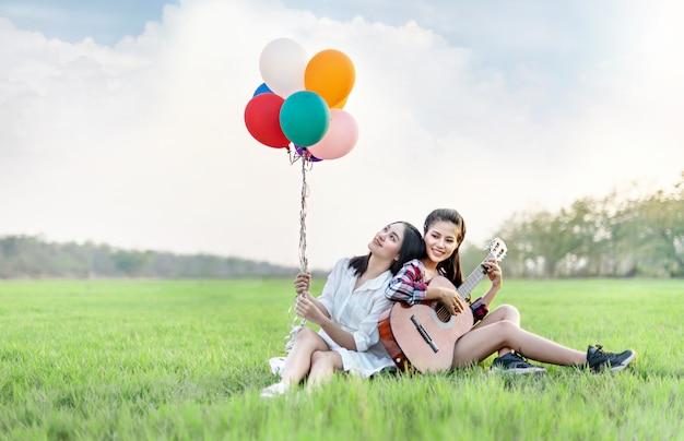 Frauen, die sich auf der grünen wiese entspannen, während sie luftballons und eine gitarre halten