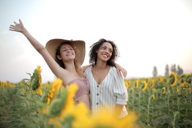 Frauen, die sich umarmen, umgeben von einem sonnenblumenfeld