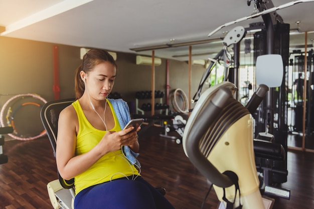 Frauen, die smartphone in der eignunggymnastik verwenden