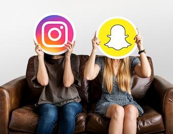 Frauen, die Social Media-Ikonen halten