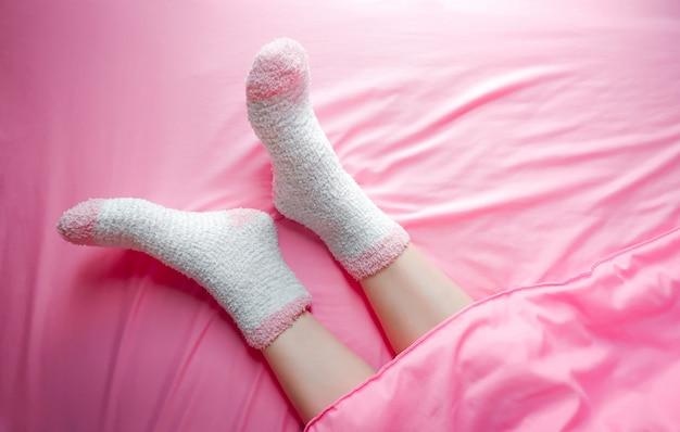 Frauen, die socken am wintermorgen und am deckenhintergrund tragen.