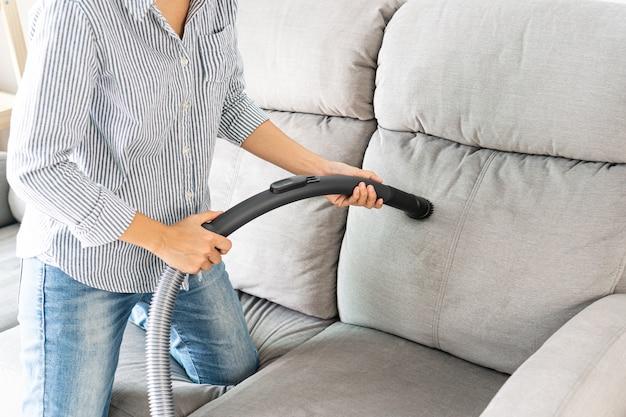 Frauen, die staubsauger-reinigungssofa im wohnzimmer zu hause verwenden. nahansicht