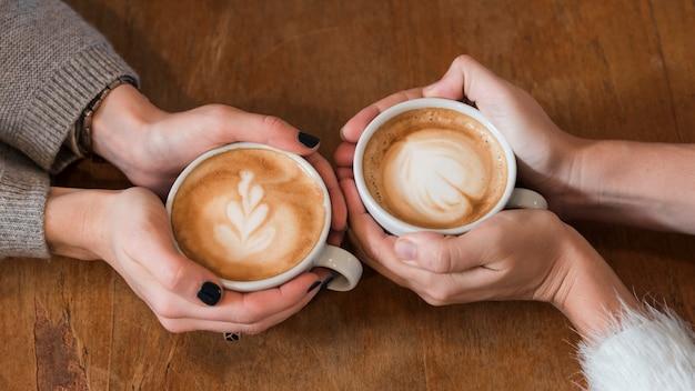 Frauen, die tasse kaffee auf tabelle halten