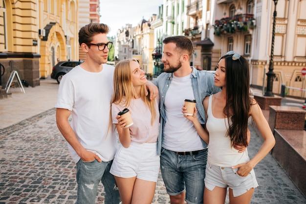 Frauen, die tasse kaffees halten und ihre freunde betrachten