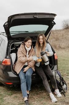 Frauen, die tee auf autoreisepause trinken