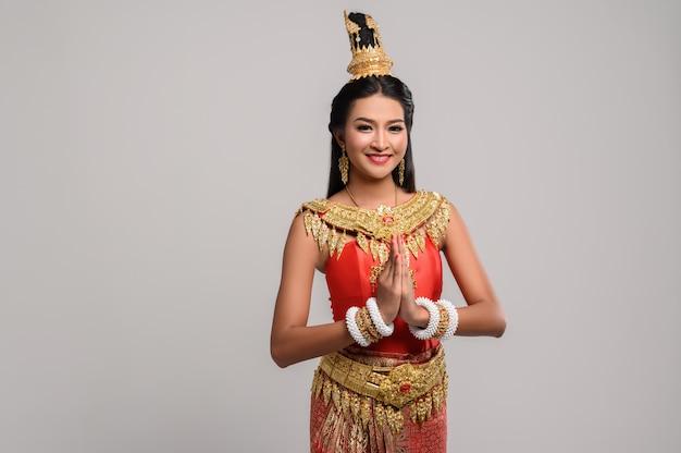 Frauen, die thailändische kleidung tragen, die respekt zahlen, sawasdee symbol