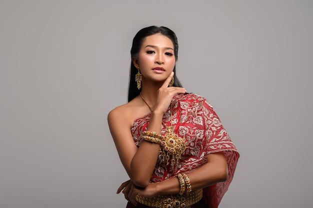 Frauen, die thailändische kleidung und hände berühren ihre gesichter tragen