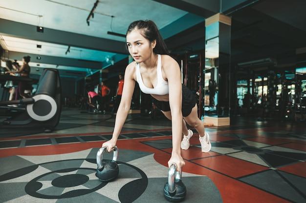 Frauen, die trainieren, indem sie den boden mit der kettlebell in der turnhalle drücken.