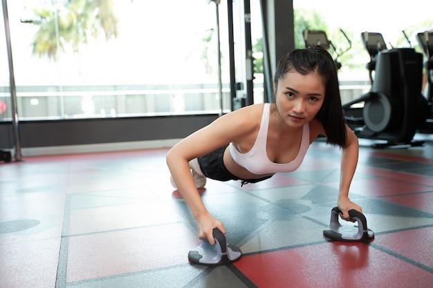 Frauen, die trainieren, indem sie den boden mit fitness push up stands in der turnhalle drücken