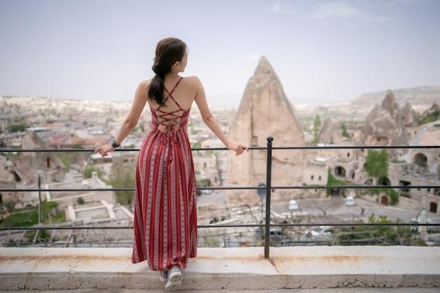 Frauen, die von der rückseite mit cappadocia-landschaft, goreme-ansichtfelsenberg, die türkei stehen