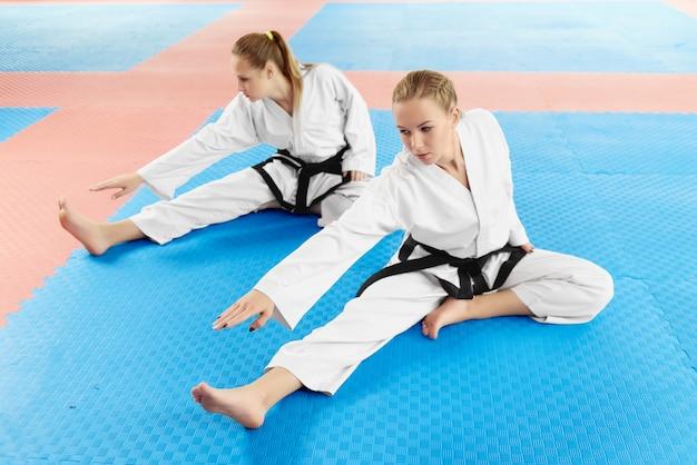 Frauen, die vor hartem training in der kampfklasse ausdehnen.