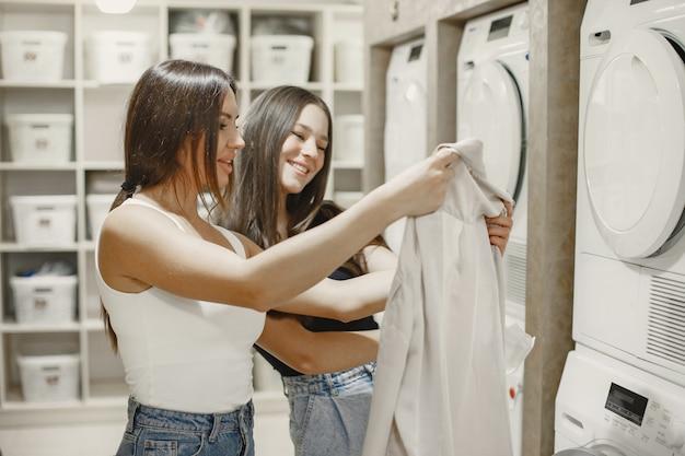 Frauen, die waschmaschine benutzen, die wäsche macht. junge mädchen bereit, kleidung zu waschen. innenraum, waschprozesskonzept