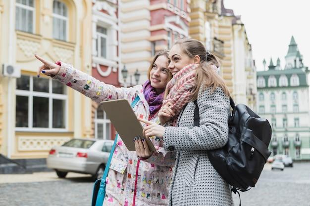 Frauen, die weg zeigen und tablette verwenden