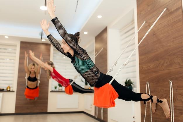 Frauen, die yoga auf den seilen ausdehnen in turnhalle üben. fit und wellness lifestyle
