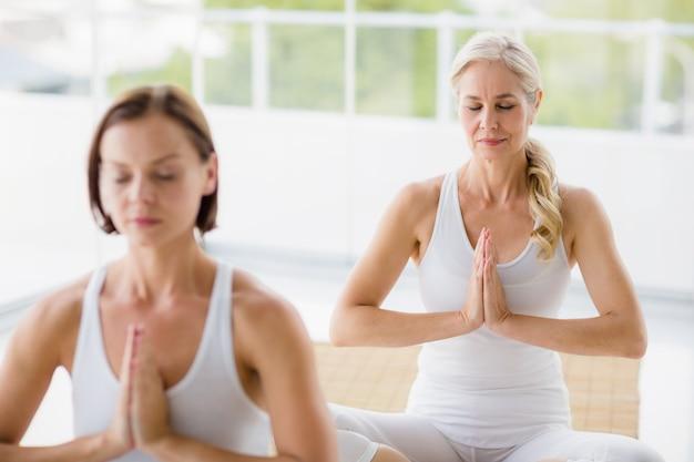 Frauen, die yoga ausführen