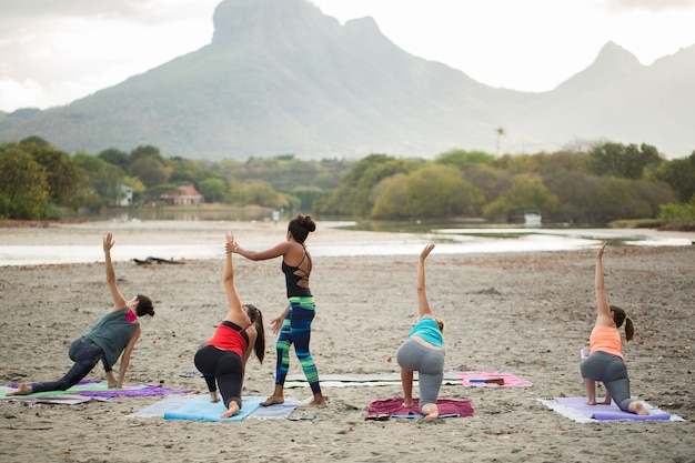 Frauen, die yogaübungen oder unterstützte taubenhaltung auf dem leeren strand des indischen ozeans in mauritius machen