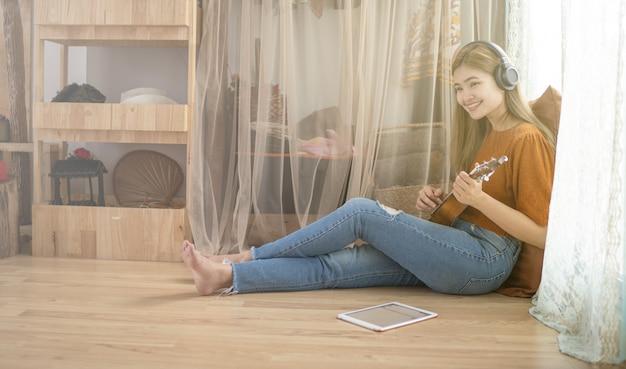 Frauen, die zu hause gitarre im wohnzimmer spielen