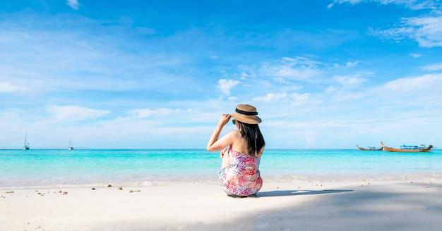 Frauen, die zurück auf dem strand und dem meer sitzen, haben einen entspannten feriensommer
