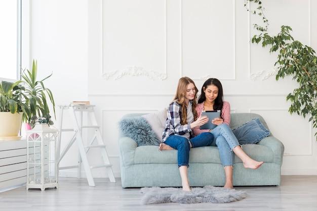 Frauen, die zusammen auf sofa sitzen und etwas in der tablette aufpassen