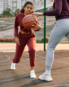 Frauen, die zusammen basketball draußen spielen