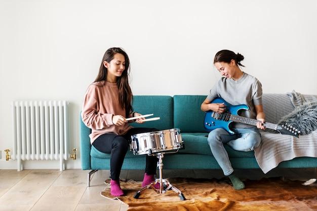 Frauen, die zusammen musik zu hause spielen