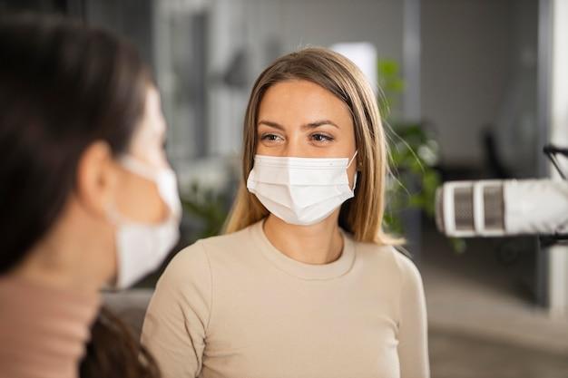 Frauen, die zusammen radio machen, während sie medizinische masken tragen