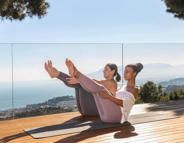 Frauen, die zusammen yoga auf der matte machen