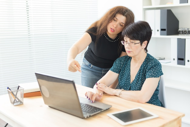 Frauen diskutieren ideen im büro mit laptop