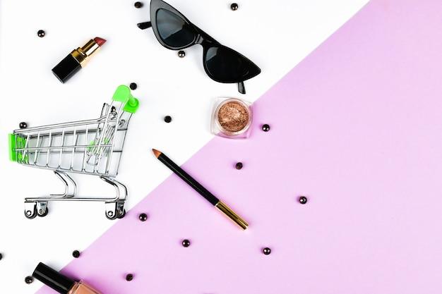 Frauen einkaufen. korb und damenaccessoires. damenaccessoires auf einem rosa raumpastell. schönheits- und modekonzept. draufsicht, flacher minimalismus.
