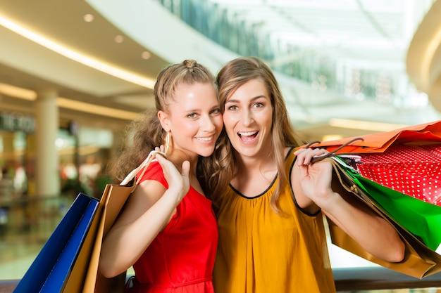 Frauen einkaufen mit taschen in einkaufszentrum
