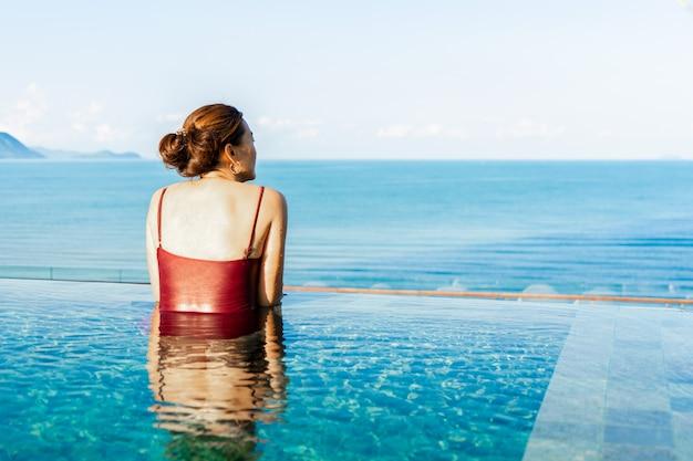 Frauen entspannen im schwimmbad mit blick auf die berge und sonnenaufgang
