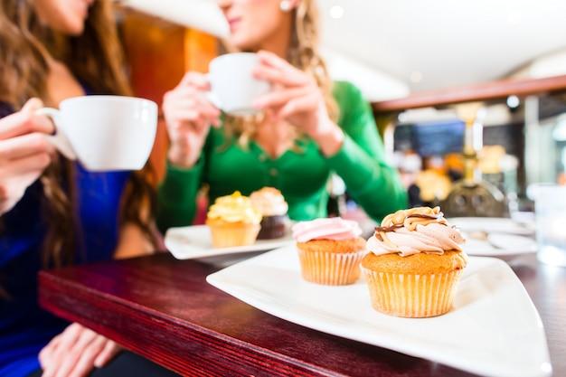 Frauen essen muffins beim kaffeetrinken