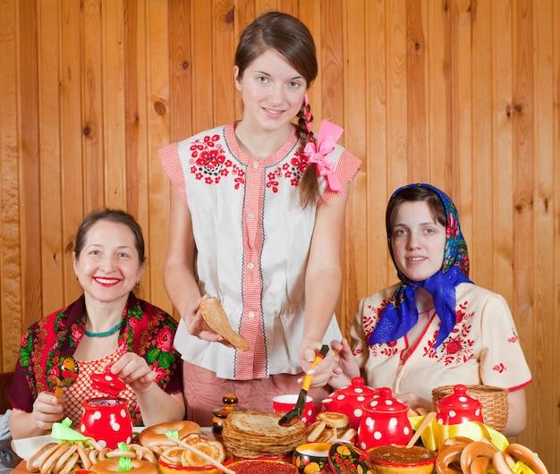 Frauen essen pfannkuchen während shrovetide