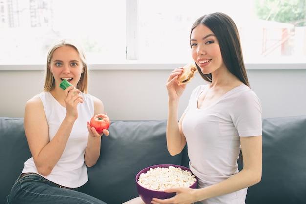 Frauen essen popcorn und gemüse