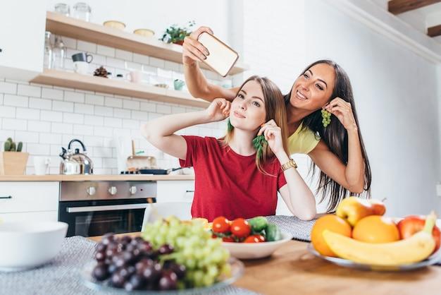Frauen essen spielen mit gemüse in der küche, haben spaß und nehmen selfie.