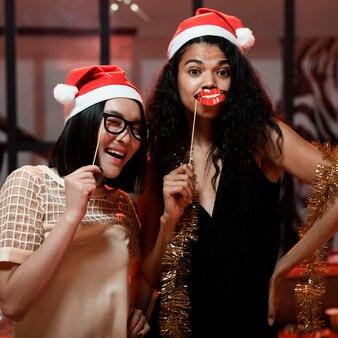 Frauen feiern mit weihnachtsmützen